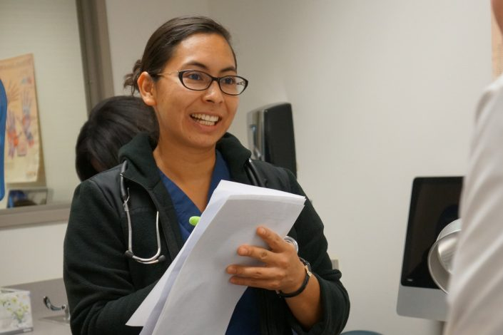 Medical Assistant student takes notes during instruction in lab