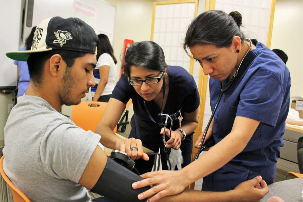 Medical Assistant students check blood pressure of test patient