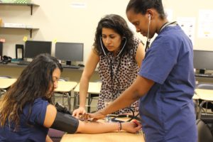 Medical Assistant students taking each other's blood pressure