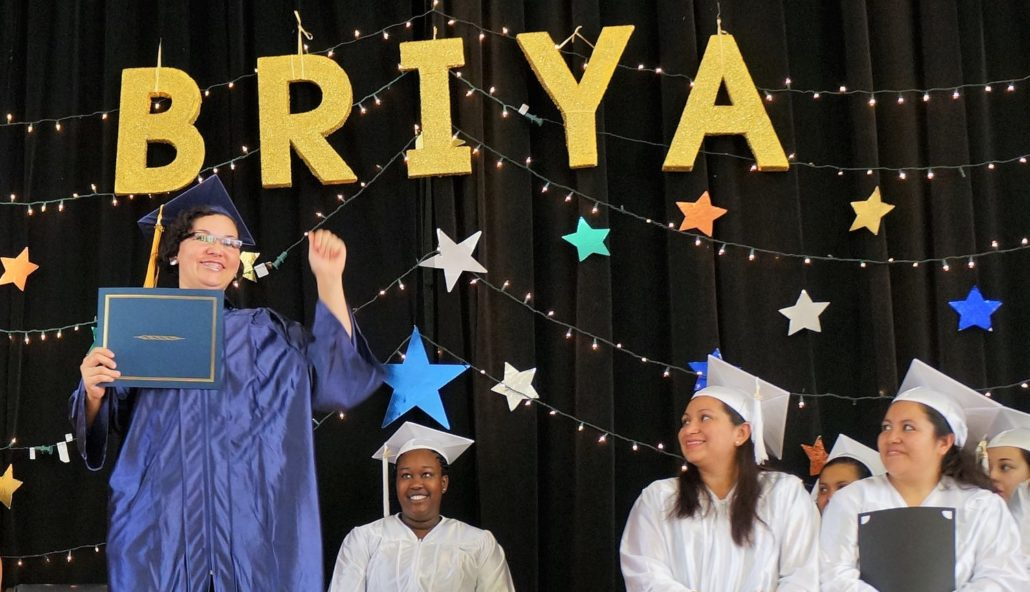 Briya graduate on stage during graduation ceremony, other students look to her as she raises her hand and holds her diploma
