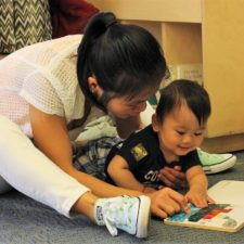 Mother reading book to infant in classroom