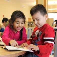 Girl and boy read together in classroom