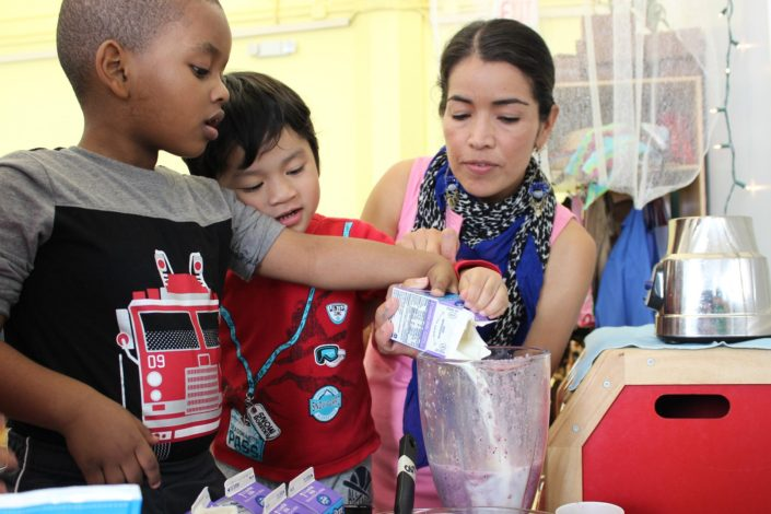 Student helps young children with cooking project