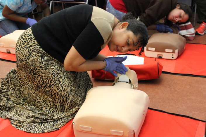 Students practice CPR on test manequins