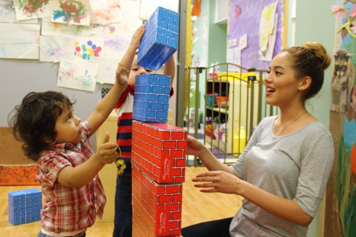 Young students play with blocks in classroom with teacher