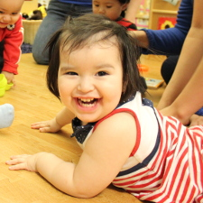Smiling infant crawling in classroom
