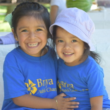 Toddler students sit and hug, in Briya t-shirts