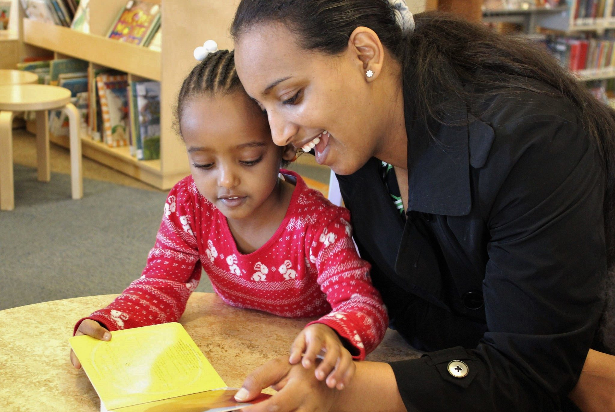 Parent reading with child in library