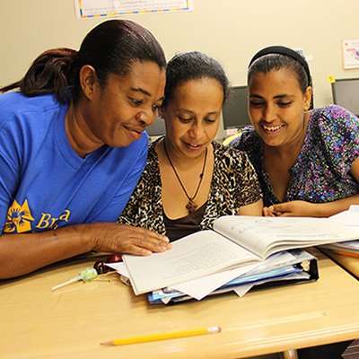 Three adult students reading together