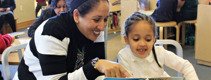 Briya staff reading a book with a young student