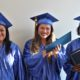 Three Briya high school graduates smiling with diplomas